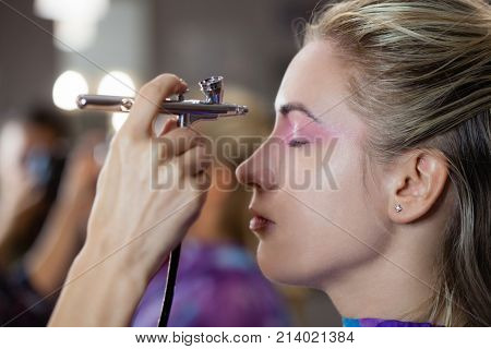 The process of making modern make up with airbrush. Makeup artist is creating and concentrated