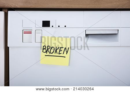 Close-up Of A Dishwasher With Adhesive Notes Showing Broken Text