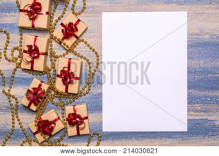 Golden beads, gifts wrapped in kraft paper with a red bow and blank paper on a wooden background. Blanched tree, blue scrapes. Flat lay concept