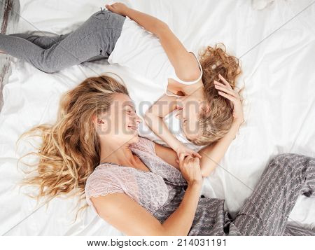 Mother with child in bed. Female and baby at home. Happy family