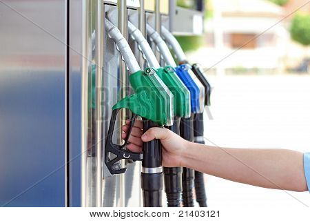 Close-up of a men's hand using a fuel nozzle at a gas station poster