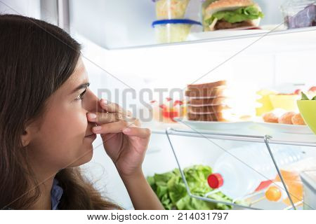 Close-up Of A Young Woman Holding Her Nose Near Foul Food In Refrigerator