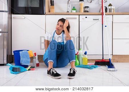 Frustrated Young Woman Sitting On Kitchen Floor And Looking At Cleaning Products At Home