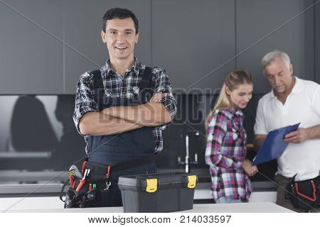 The plumber is posing in the kitchen. He stands cross-arms and smiles. Behind him is a client and communicates with the second plumber. A black toolbox is next to it.