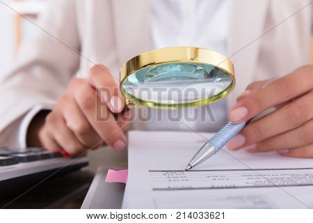Close-up Of Businesswoman Checking Invoice With Magnifying Glass At Desk