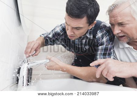Two plumbers repair the faucet in the bathroom. One of them replaces the tap, the second one teaches the junior sanitary technician. On the young plumbers special uniform.