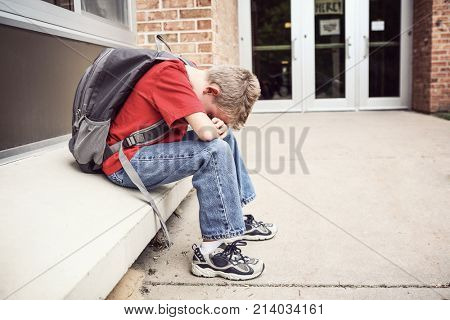 Depressed student sitting outside of school hiding his face