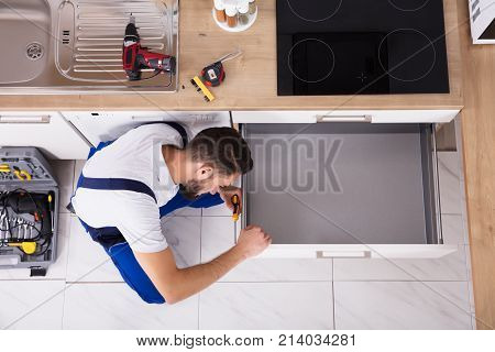 High Angle View Of Male Carpenter Fixing Drawer In Kitchen