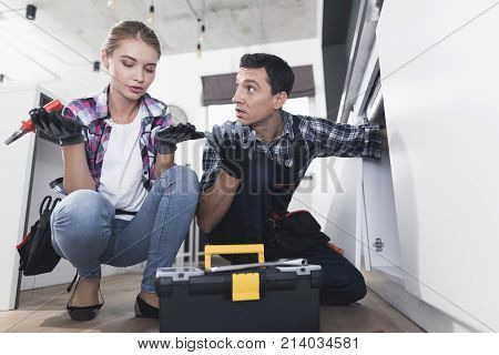 A man and a woman plumber repair a sink in the kitchen in the kitchen. A man repairs pipes, a woman helps him and monitors work.