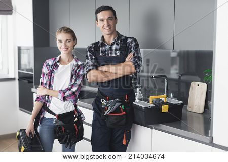 A man and a woman plumber will be cheated in the kitchen. They have just successfully repaired the sink for the customer. Next to them is a black box with a tool.