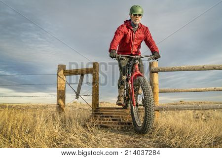 a senior male is riding a mountain fat bike over a cattle guard in Soapstone Prairie Natural Area in northern Colorado, late fall scenery