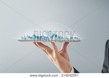 Waiter hand holding an empty digital tablet with smart cityscape and network connection concept . Isolated on grey background .