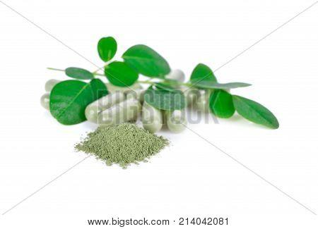 fresh moringa leaves ground and capsule herbal on white background