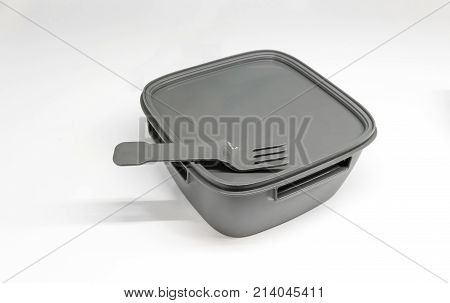 Grey Plastic Lunch Box With Fork On Top Of The Rubber Lid Isolated On White Background.