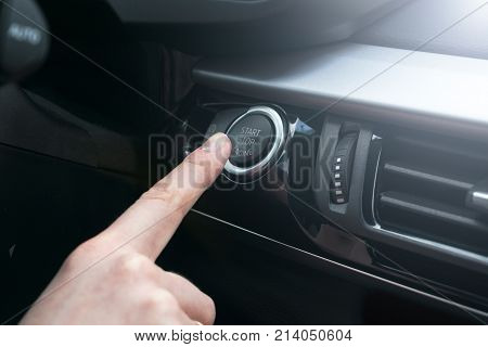 Finger press button functions car engine start and stop in motor vehicle for pre start checklist concept. Modern car interior details. Soft lighting