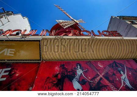 PARIS, FRANCE - CIRCA JUNE 2014: Famous cabaret Moulin Rouge with windmill on rooftop on sunny day