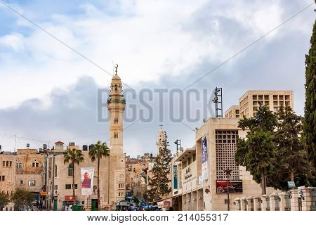 Buildings of Bethlehem city with flags and ads on walls, cloudy sky in background