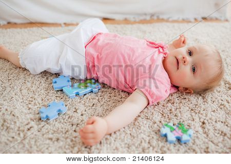 Cute Blond Baby Playing With Puzzle Pieces While Lying On A Carpet