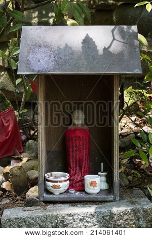 Iga Ueno - Japan, June 1, 2017: Traditional stone carved Jizo with red skirt honored and respected with a cup of water and incense in Ueno park