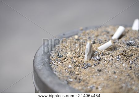 Details of smoked cigarettes in a dirty ashtray