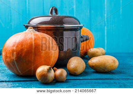 Photo of iron pot with lid, vegetables, potatoes, pumpkins, onions on blue wooden phone