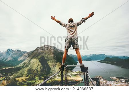 Man raised hands balancing at the edge cliff Rampestreken landmark in Norway mountains Travel lifestyle risk concept active vacations happy tourist enjoying landscape aerial view