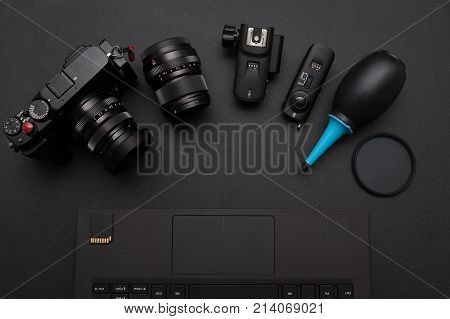top view of photographer work space with mirrorless camera system, Dust blower, Lens filter, Wireless flash trigger, and card on laptop