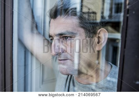close up portrait of sad and depressed 40s man looking through window glass reflection lonesome and thoughtful suffering depression thinking and feeling low in life crisis and problem concept poster