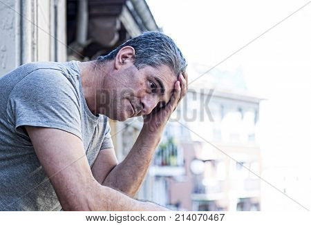 close up portrait of sad and depressed 40s man looking through outdoors at home balcony lonesome and thoughtful suffering depression thinking and feeling low in city buildings urban background