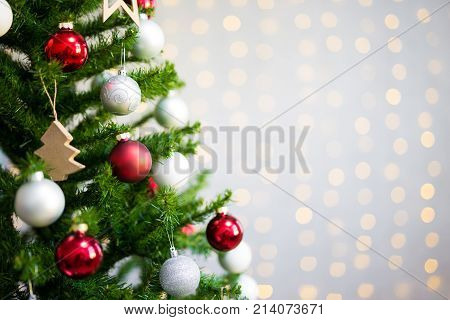 Close Up Of Decorated Christmas Tree Over White Brick Wall With Lights