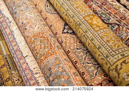 Variety of colorful Persian and Indian carpets on oriental bazaar