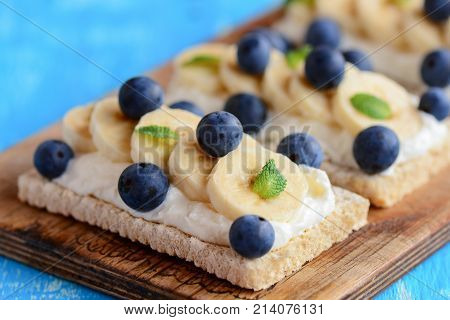 Homemade crispbread toast with cottage cheese, banana and berries on wooden board. Cottage cheese sandwich idea. Closeup