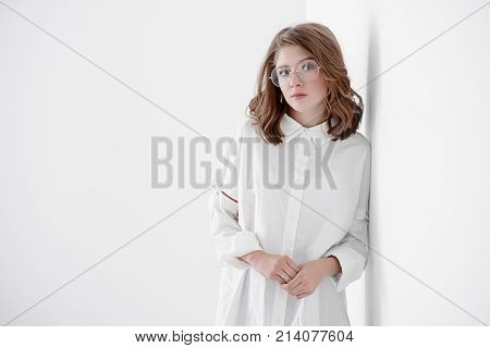 Portrait of a cute girl teenager in spectacles leaned against the white wall. Glasses for a modern young generation. Beauty, fashion.