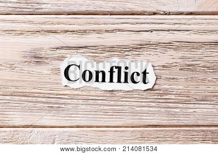Conflict of the word on paper. concept. Words of Conflict on a wooden background.