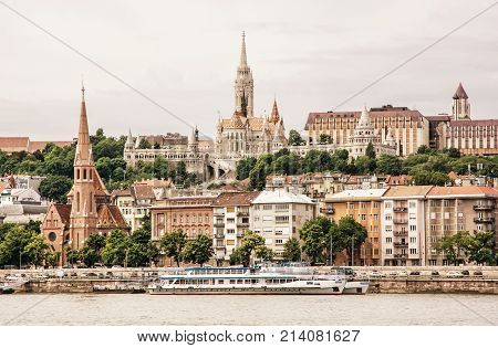 Matthias church Fishermans bastion and Calvinist church in Budapest Hungary. Cultural heritage. Architectural theme. Danube river bank with cruise ships. Old photo filter.
