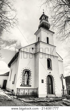 Baroque-Classicist Roman-Catholic church of the Marys Visitation in Vlkolinec village Slovak republic Unesco. Religious architecture. Black and white photo.