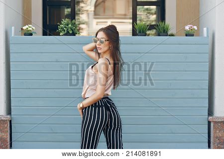 Beautiful Woman, Wearing Dark Glasses, Against The Background Of A Tree Wall. The Model Wears Stylis