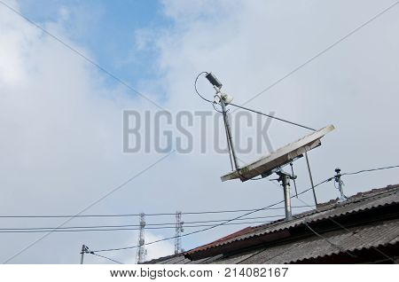 Modern high technology satellite on a roof with cloudy sky