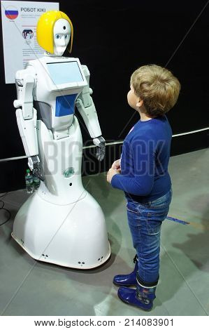 MOSCOW, RUSSIA - NOVEMBER 8, 2017: A boy communicates with the robot girl Kiki at the exhibition.