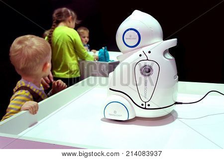 MOSCOW, RUSSIA - NOVEMBER 5, 2017: The little boy at the exhibition with the children's robot babysitter UNO.