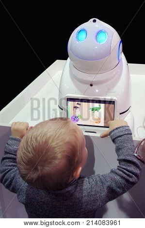 MOSCOW, RUSSIA - NOVEMBER 5, 2017: The boy plays with the children's robot babysitter UNO