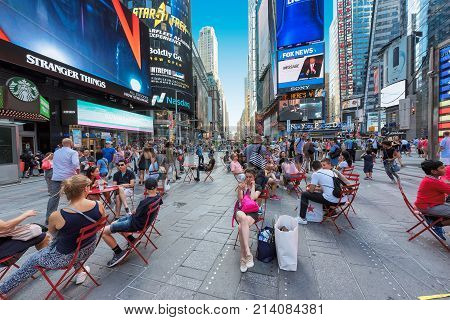 People relax in Times Square on a Sunny day on July 30, 2017 in Manhattan, New York. Times Square is a busy tourist intersection and is an iconic street of New York.