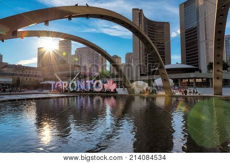 Toronto City Hall and Nathan Phillips Square at sunset on June 28, 2017 in Toronto, Canada. people walk by Toronto sign at sunset.