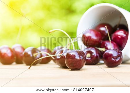 Cherries on wooden table with green bokeh background