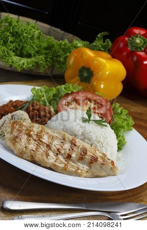 Baked chicken breast with rice, beans and salad