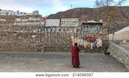 Yushu, China - November 3, 2017: Tibetan Monk Praying In Front Of Mani Stones At The Mani Temple (ma