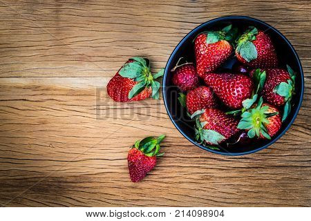 Strawberries With Black Bowl On Wooden Table