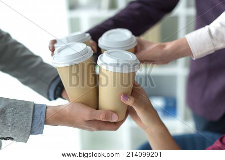 Cropped image of business partners clinking disposable coffee cups