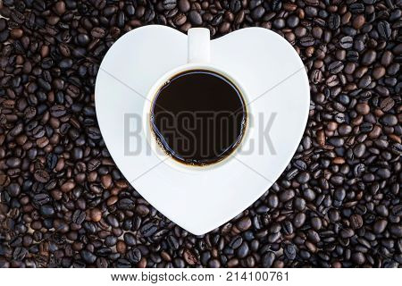 Coffee Cup With Heart Shaped Saucer On Coffee Beans