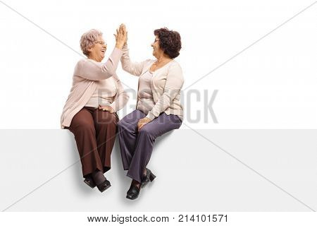 Two elderly women sitting on a panel and high-fiving each other isolated on white background